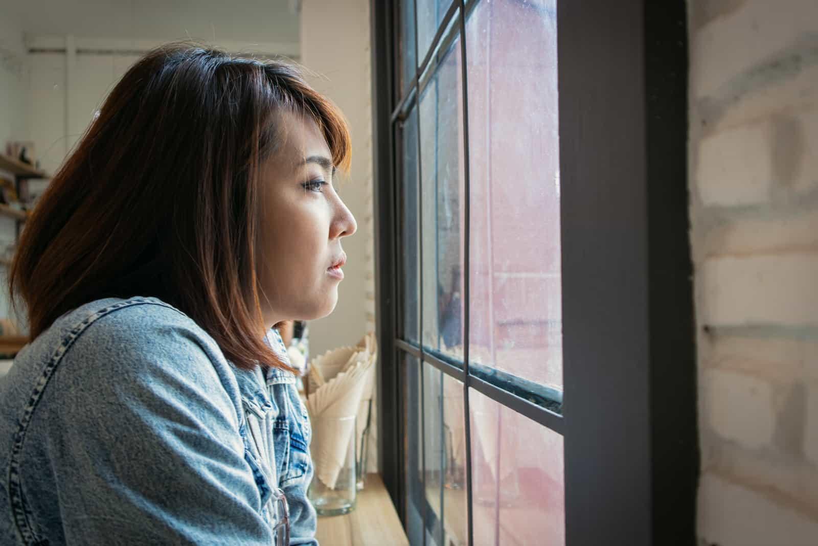 sorglig kvinna bakom fönstret