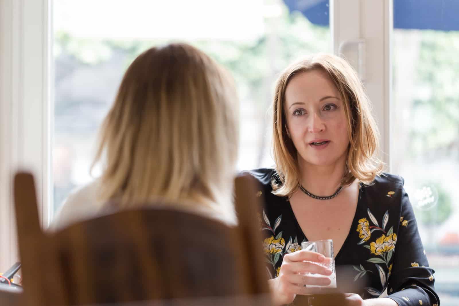 två kvinnavänner som sitter vid bordet och pratar