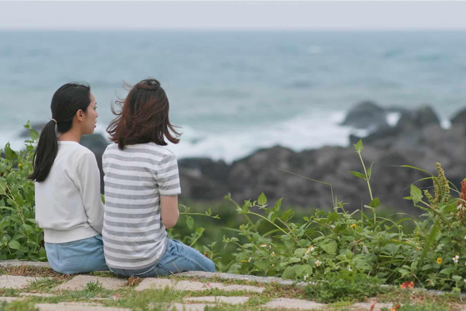 två ung kvinna som sitter i naturen och pratar