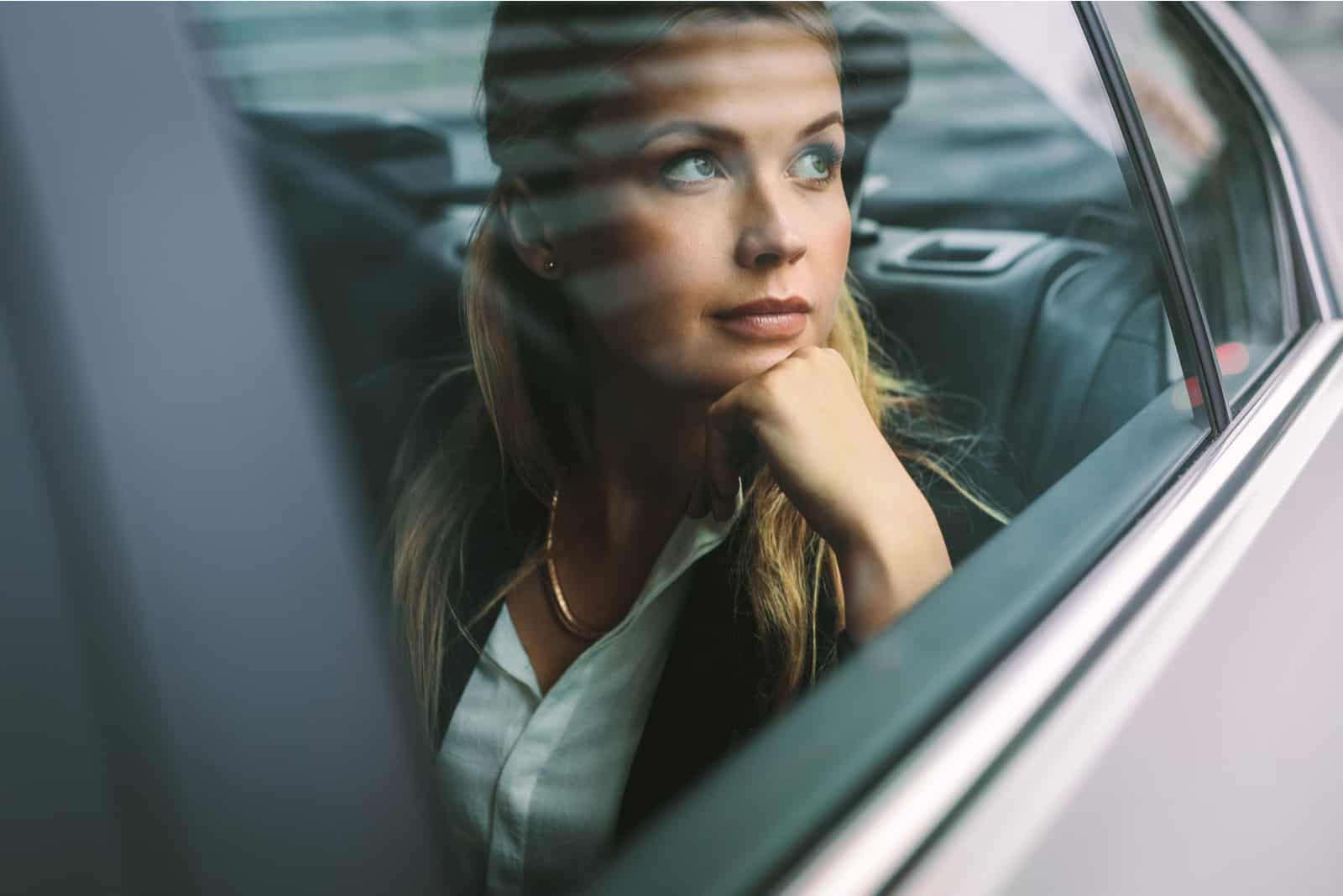 ung affärskvinnasammanträde på baksätet i en bil