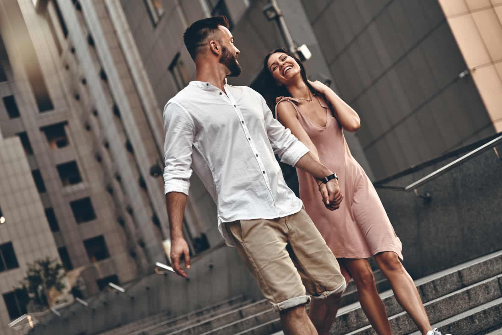ungt par som håller hand och ler