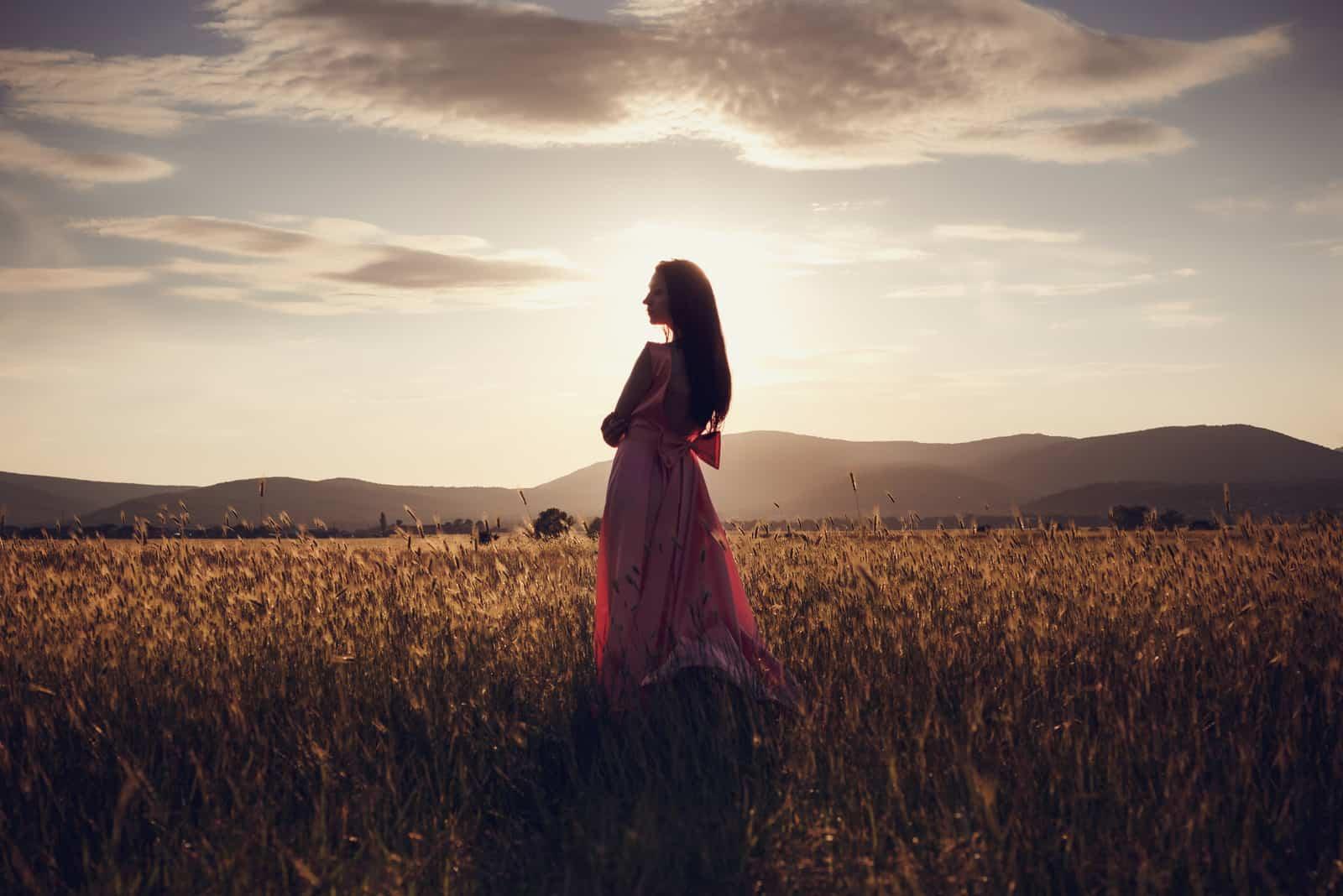 vacker kvinna som går på vetefält före solnedgången
